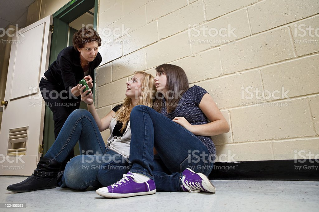 Teenage students disturbing a class with their cel phone use royalty-free stock photo