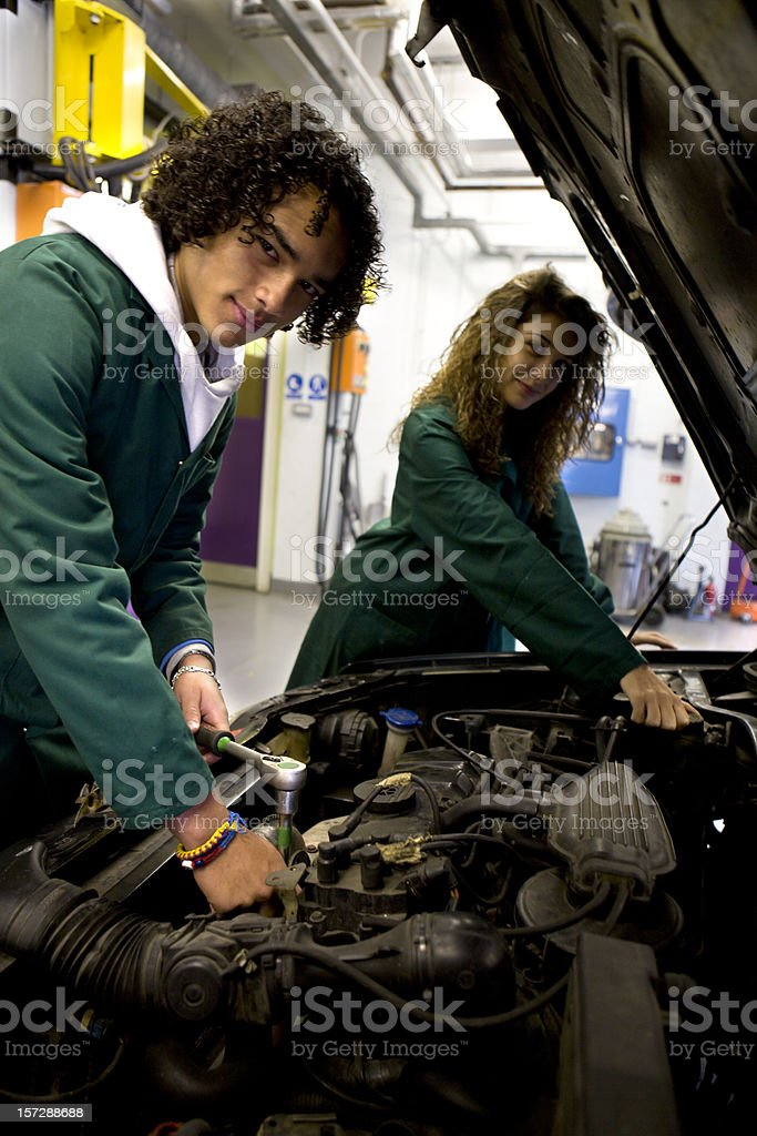 teenage students gaining practical experience studying engines in a garage royalty-free stock photo