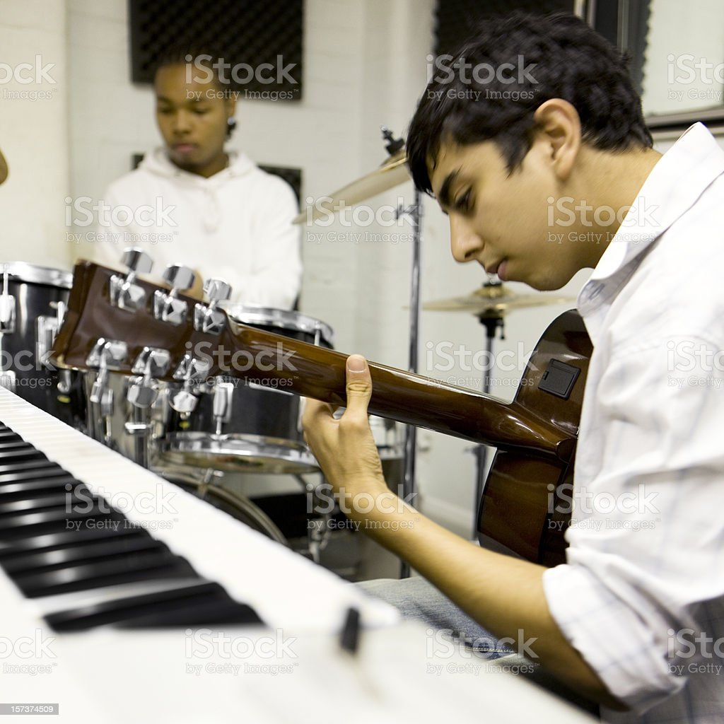 teenage students rehearsing in a music studio together stock photo