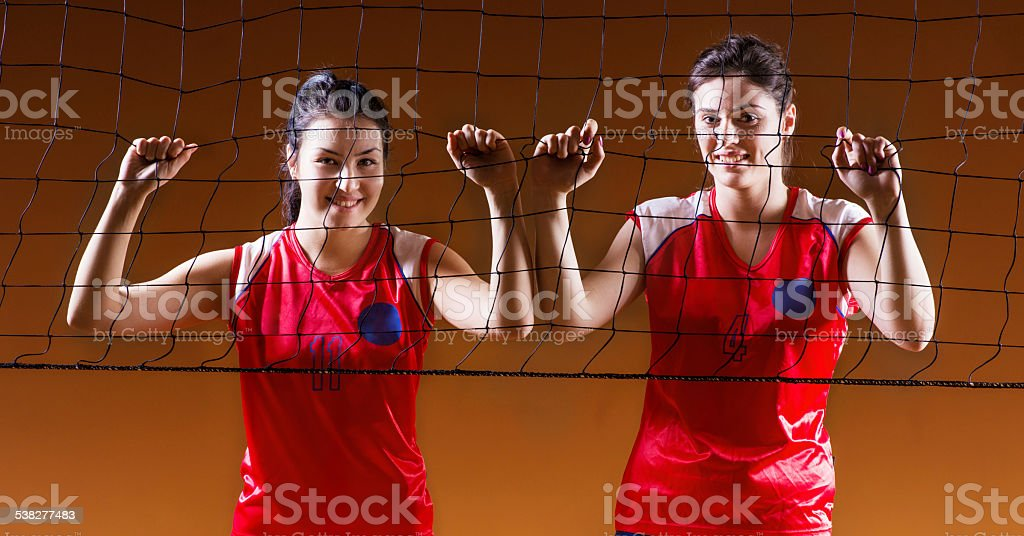 Teenage volleyball players on the net. stock photo