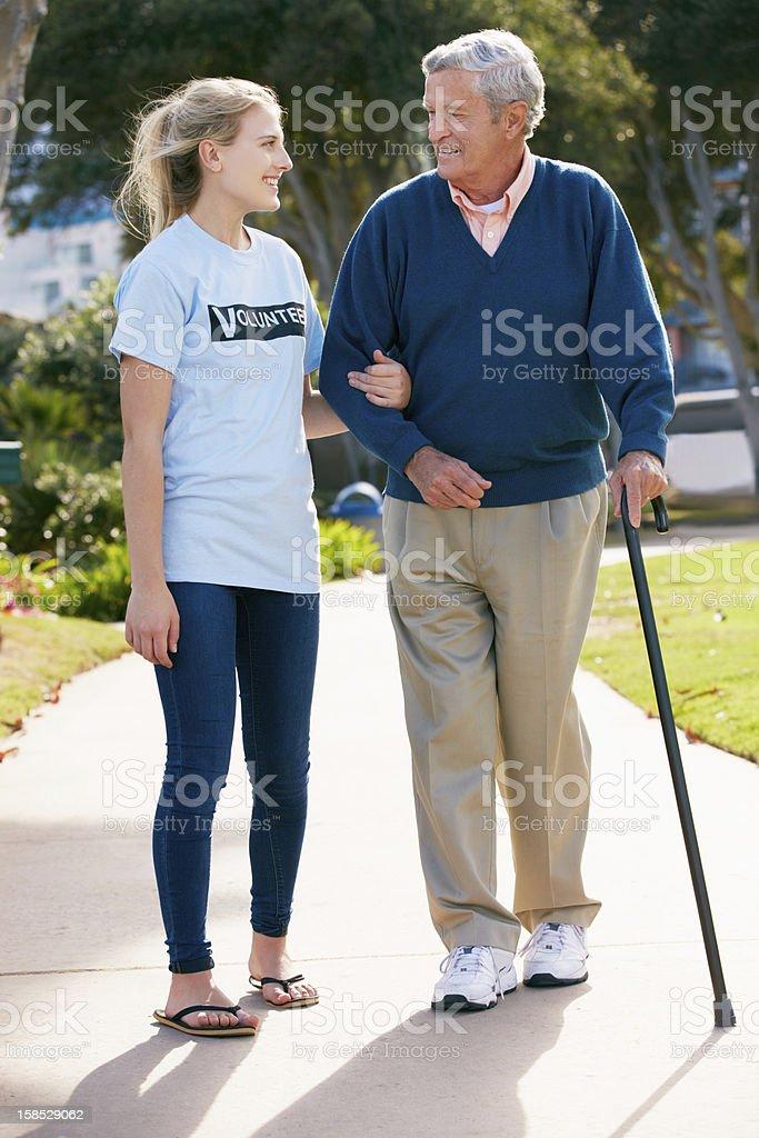 Teenage Volunteer Helping Senior Man Walking Through Park stock photo