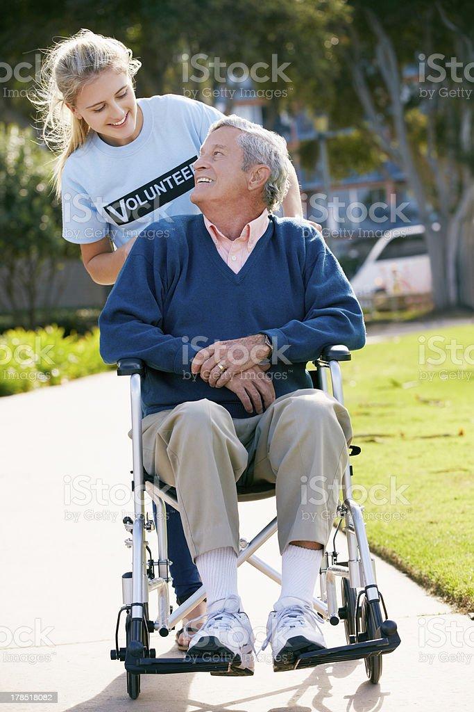 Teenage Volunteer Pushing Senior Man In Wheelchair royalty-free stock photo