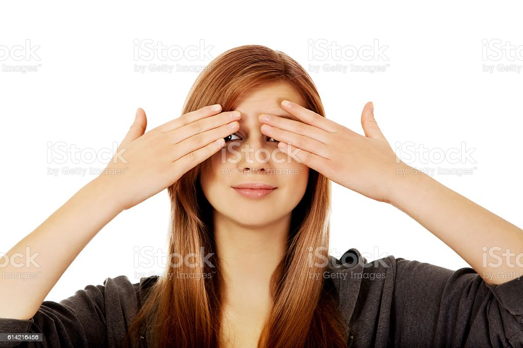 Teenage woman covering her eyes with both hands stock photo