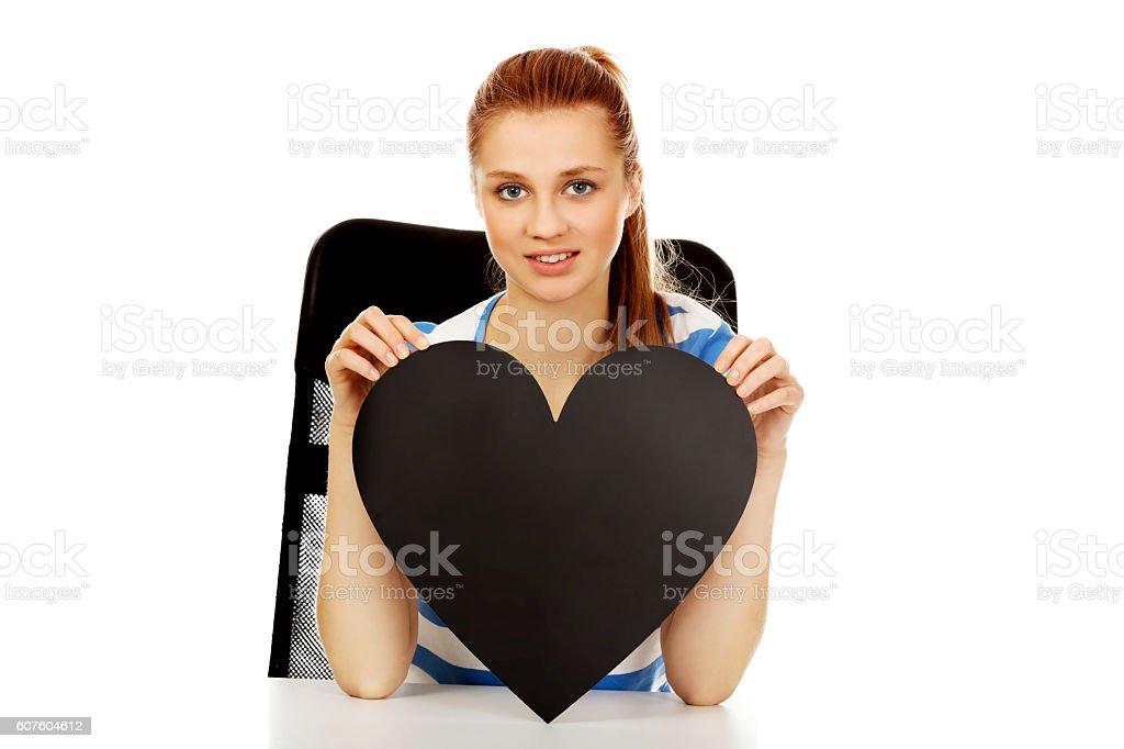 Teenage woman holding black paper heart stock photo