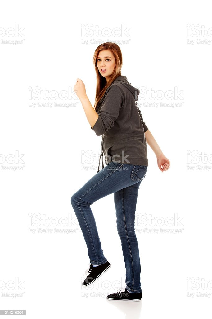 Teenage woman trying to trample something stock photo