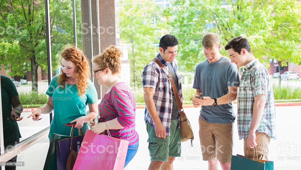 Teenage, young adult friends downtown shopping.  Bags. stock photo