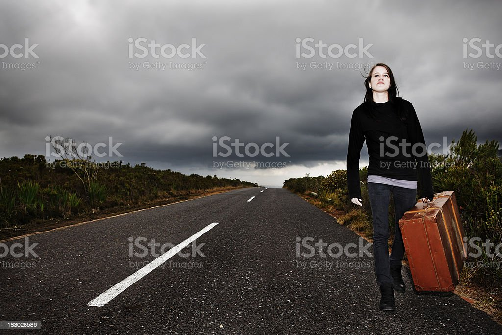 Teenaged girl with suitcase walks along road under ominous sky royalty-free stock photo