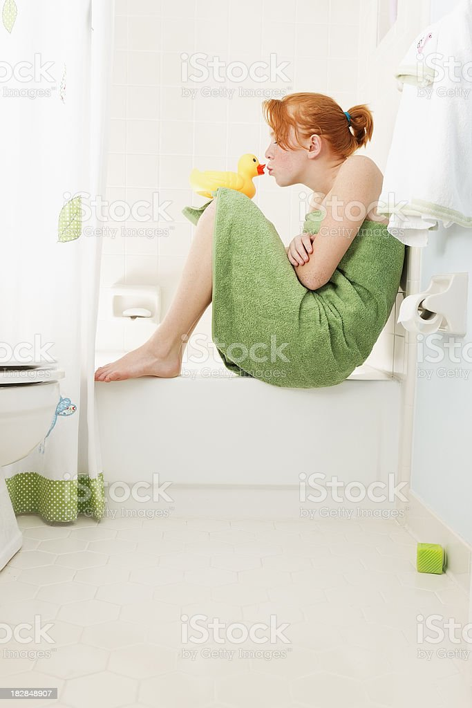 Teenaged redheaded girl and her rubber ducky friend. royalty-free stock photo