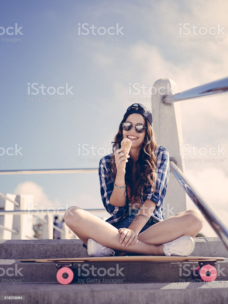 Teenaged skater girl with ice cream cone on summer day stock photo