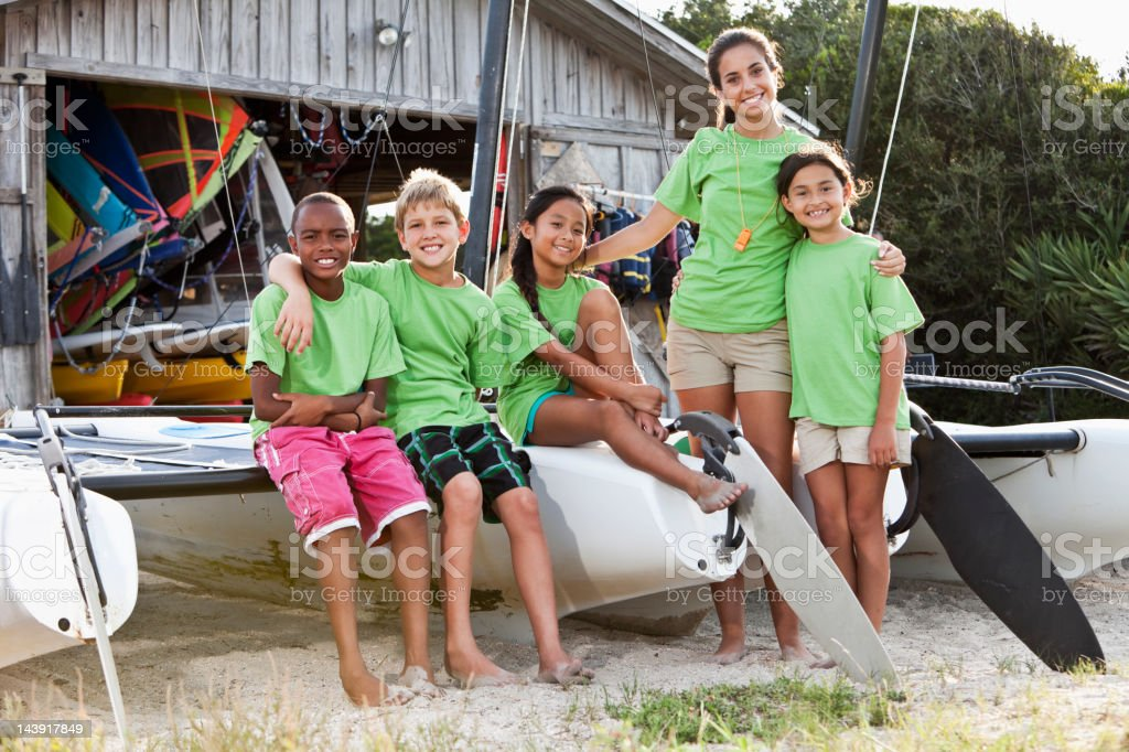 Teenager and children in front of water sports equipment shack stock photo