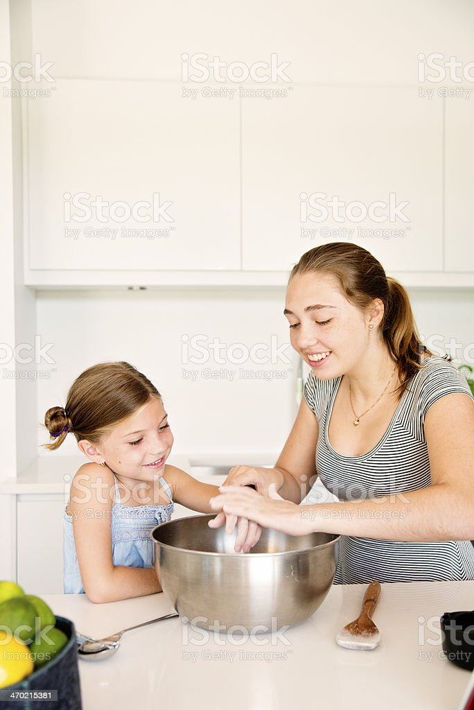 Teenager and little girl cooking together with copyspace. royalty-free stock photo