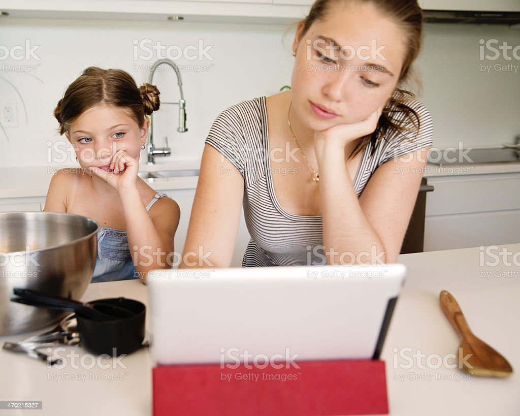 Teenager and little girl searching online to find recipe. royalty-free stock photo