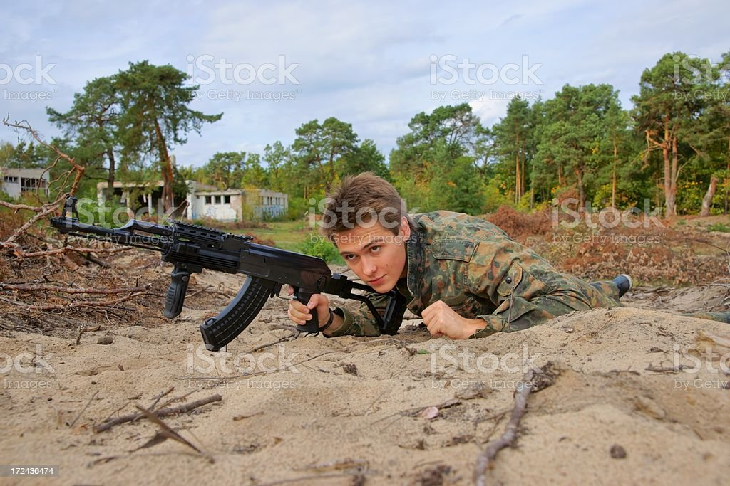 Teenager, boy crawling in uniform and with a rifle stock photo