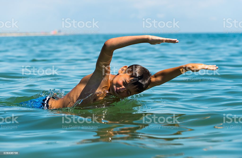 Teenager  boy enjoying a swimming in the sea stock photo