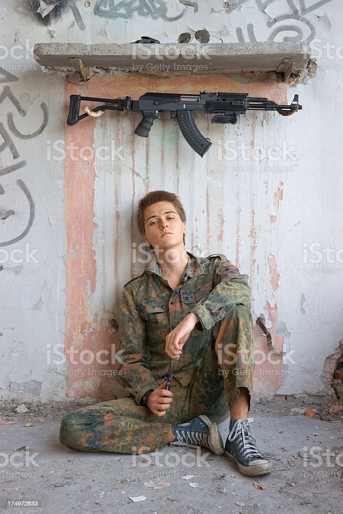 Teenager, boy in battle dress, of knife and rifle stock photo