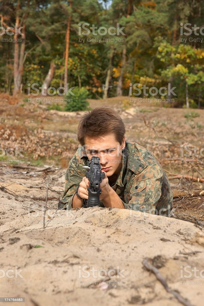 Teenager, boy lying in his battle dress and a rifle stock photo