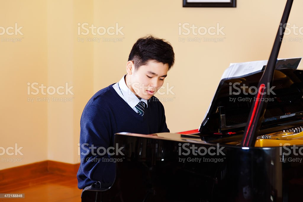 teenager boy playing piano stock photo