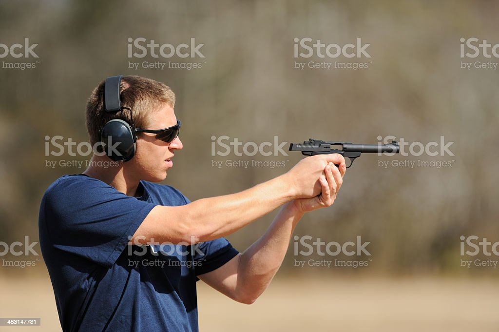 Teenager boy shooting pistol handgun royalty-free stock photo