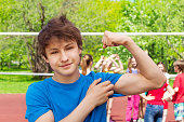 Teenager boy shows bicep muscles on the playground