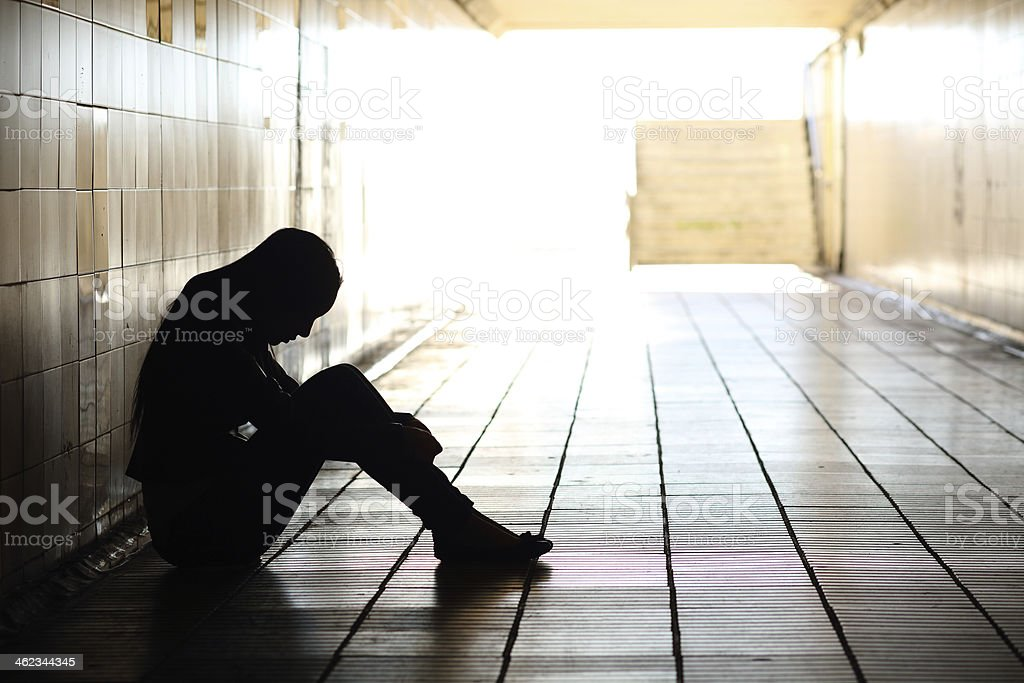 Teenager depressed sitting inside a dirty tunnel stock photo