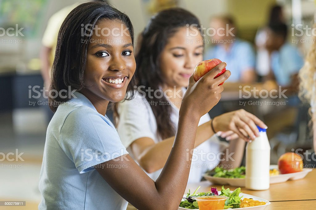 Teenager eating healthy lunch with friends in school lunchroom stock photo