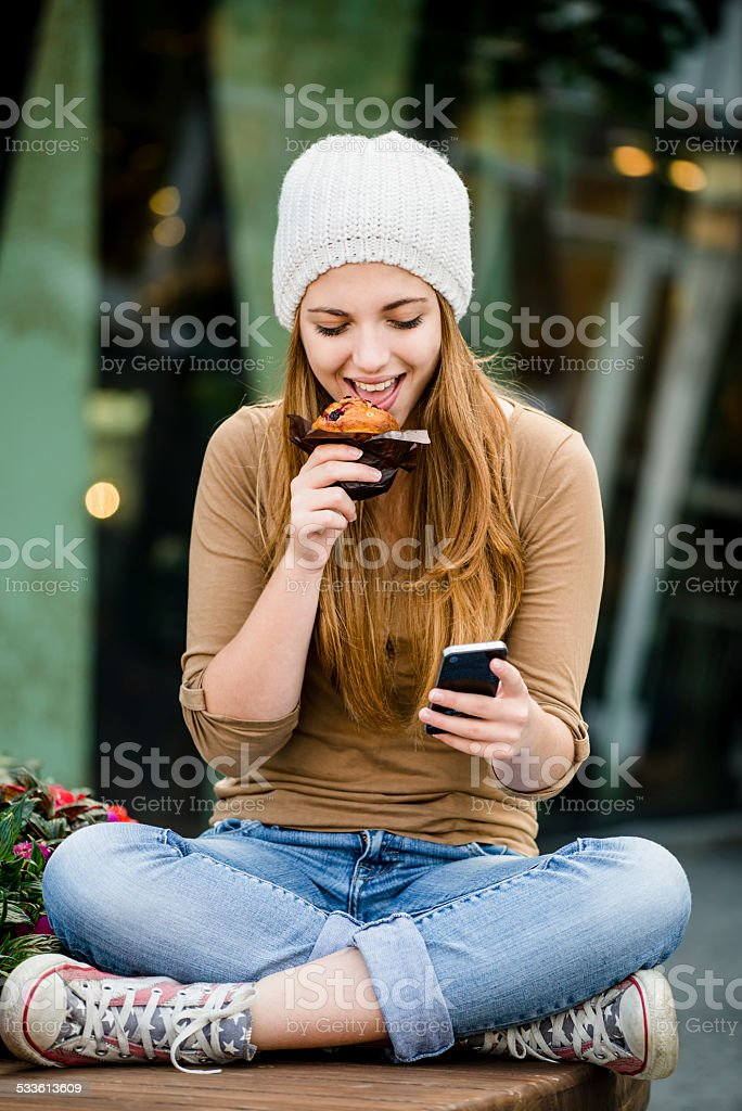 Teenager eating muffin looking in phone stock photo