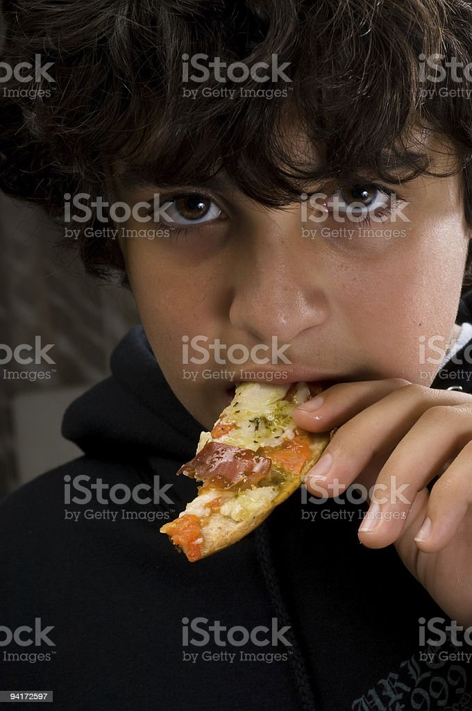Teenager eating prosciutto pizza stock photo