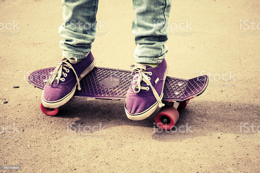 Teenager feet in jeans and gumshoes on skateboard stock photo