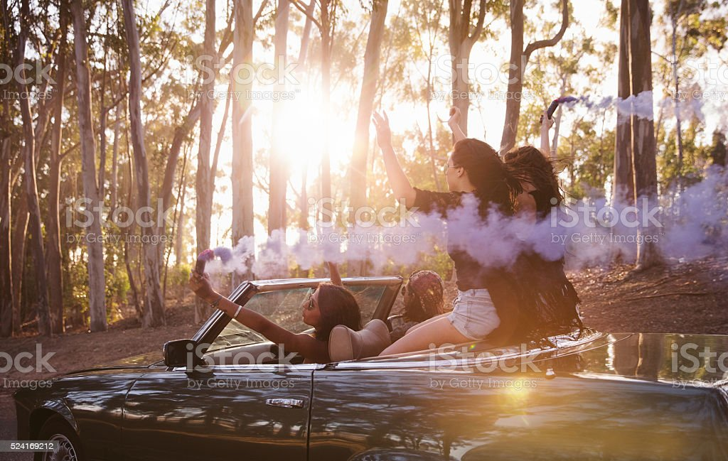 Teenager friends celebrating their road trip with smoke bombs stock photo