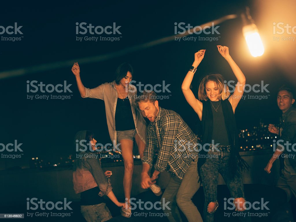 Teenager friends dancing and laughing on a rooftop party stock photo