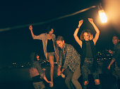 Teenager friends dancing and laughing on a rooftop party
