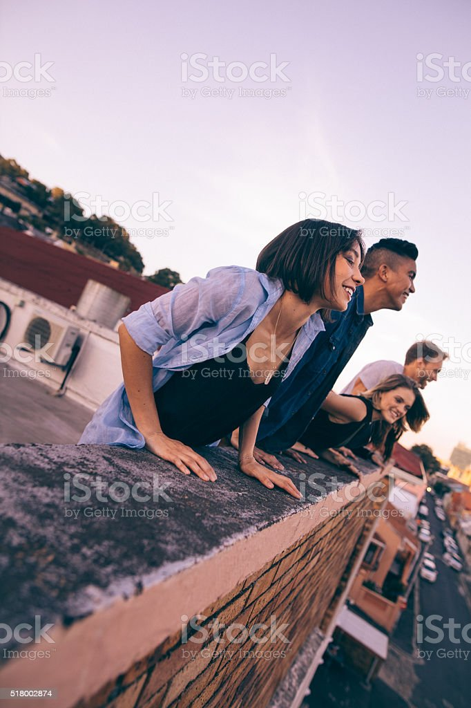 Teenager friends laughing over the city from a  rooftop stock photo
