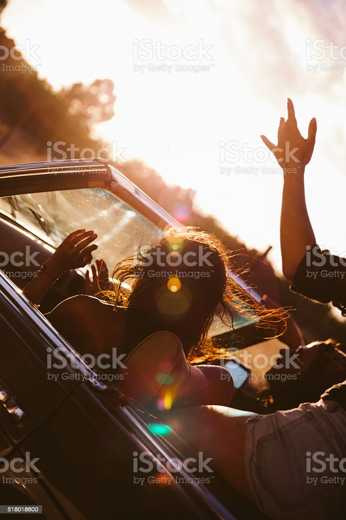 Rear view of a teenager girl enjoyng a road trip on a convertible car...