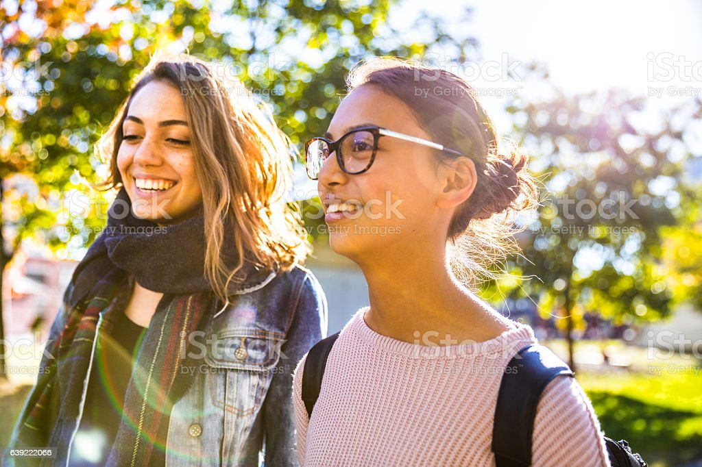 Teenager friends walking down the city going to school stock photo
