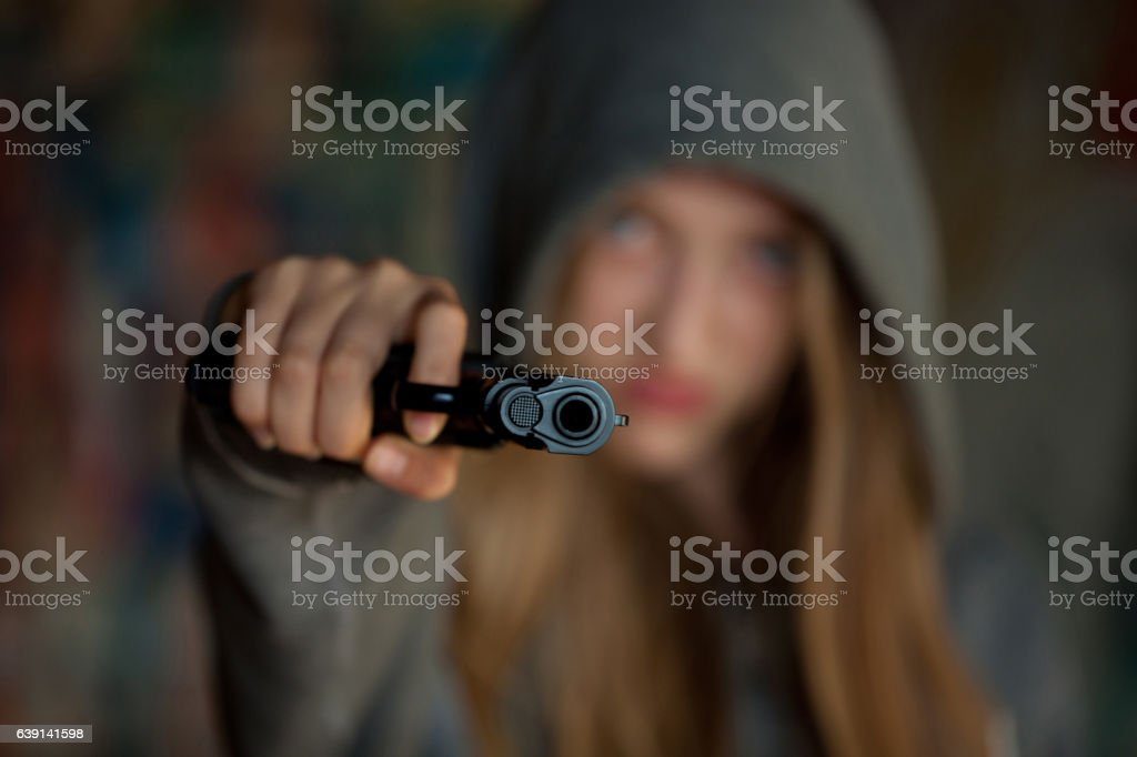 Teenager Girl Aiming a gun at the camera,, blurred focus stock photo