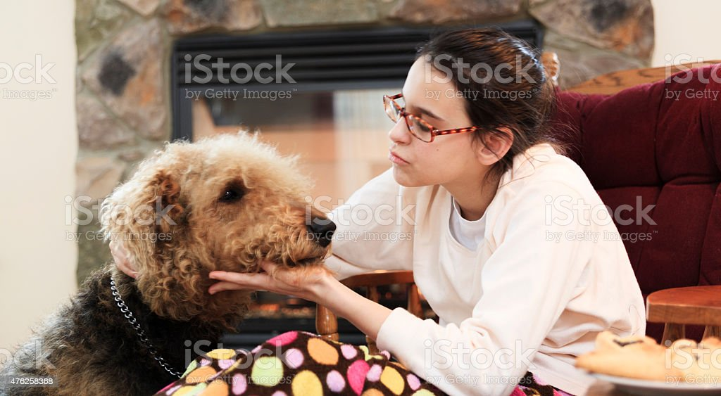 Teenager girl and dog in living room stock photo