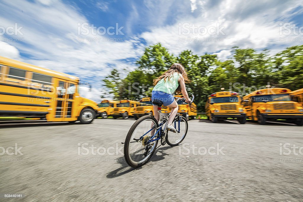 Teenager girl cycling next to school buses royalty-free stock photo
