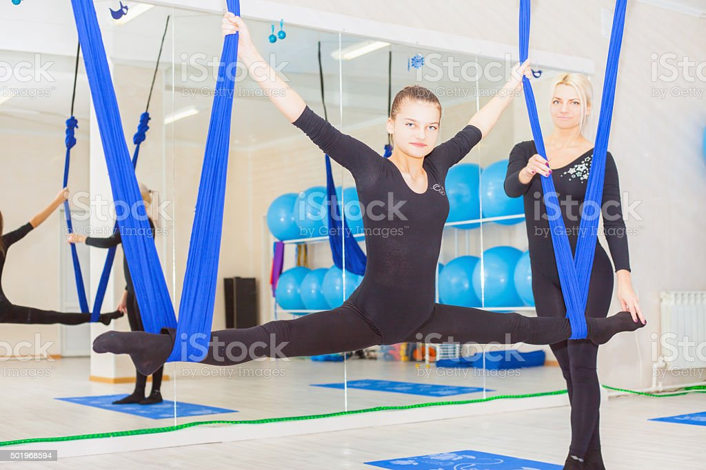Teenager girl doing stretching and twine, aerial yoga stock photo