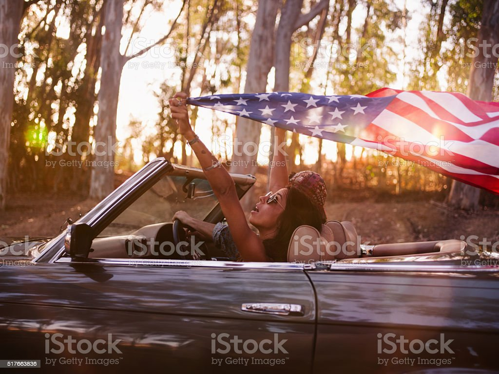 Teenager girl holding an American flag on a road trip stock photo