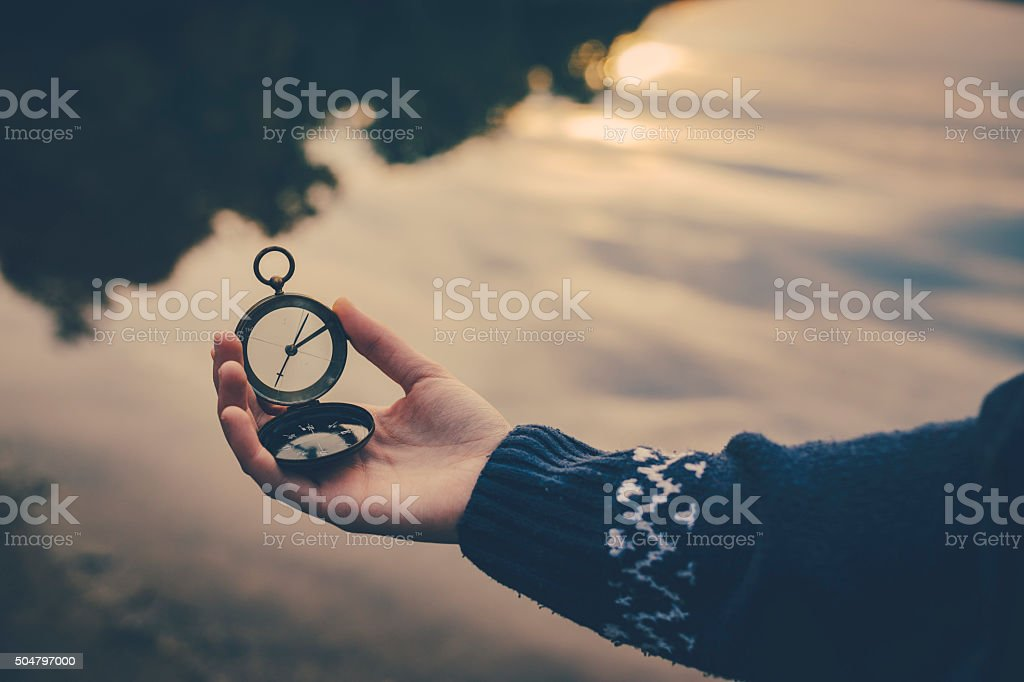 Teenager girl  holding an old compass in hand stock photo