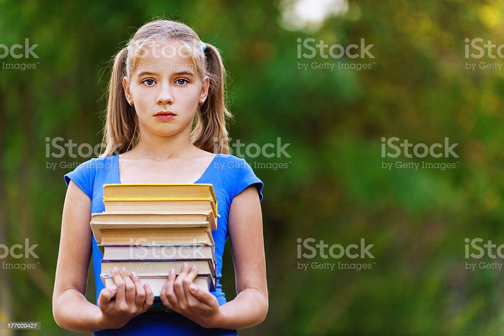 Teenager girl holding stack of seven books royalty-free stock photo