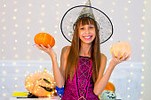 Teenager girl in witch costume posing with pumpkins