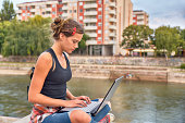 Teenager girl looking at a laptop in the city
