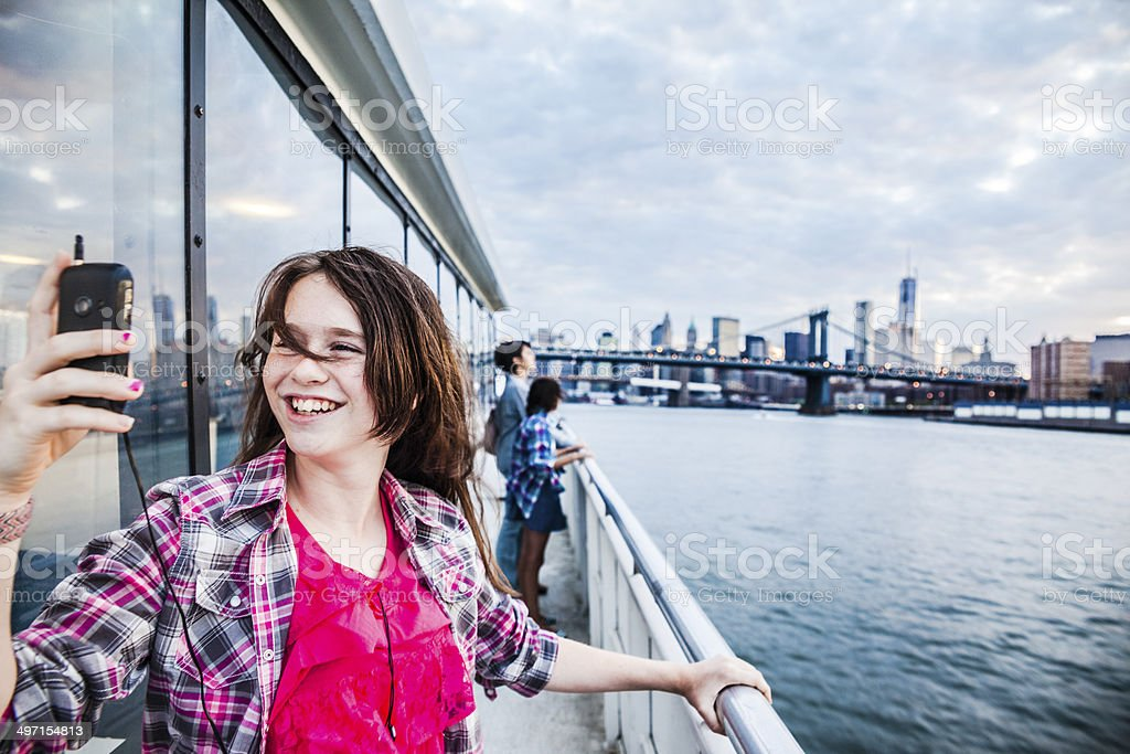 Teenager girl make selfie at ferry in front of Manhattan stock photo