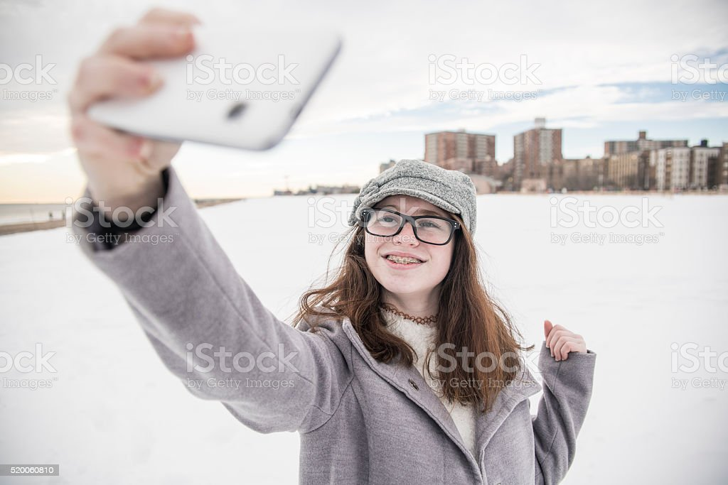 Teenager girl make selfie at the snowy beach stock photo