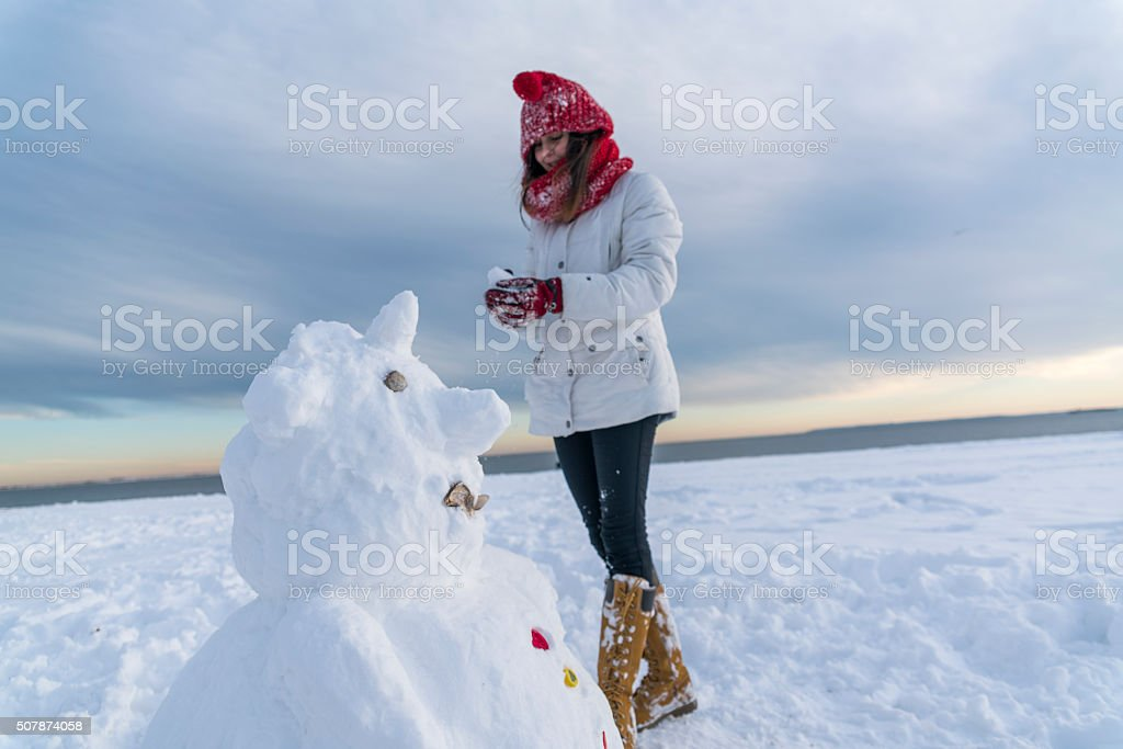Teenager girl make the snowman at the beach stock photo