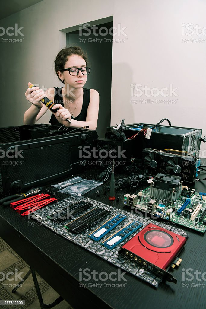 Teenager girl - nerd and geek - trying to assemble stock photo