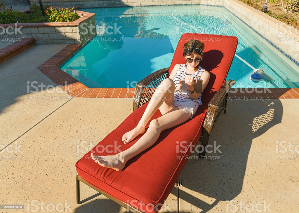 Teenager girl reading tablet while sitting in the red chaise lounge...