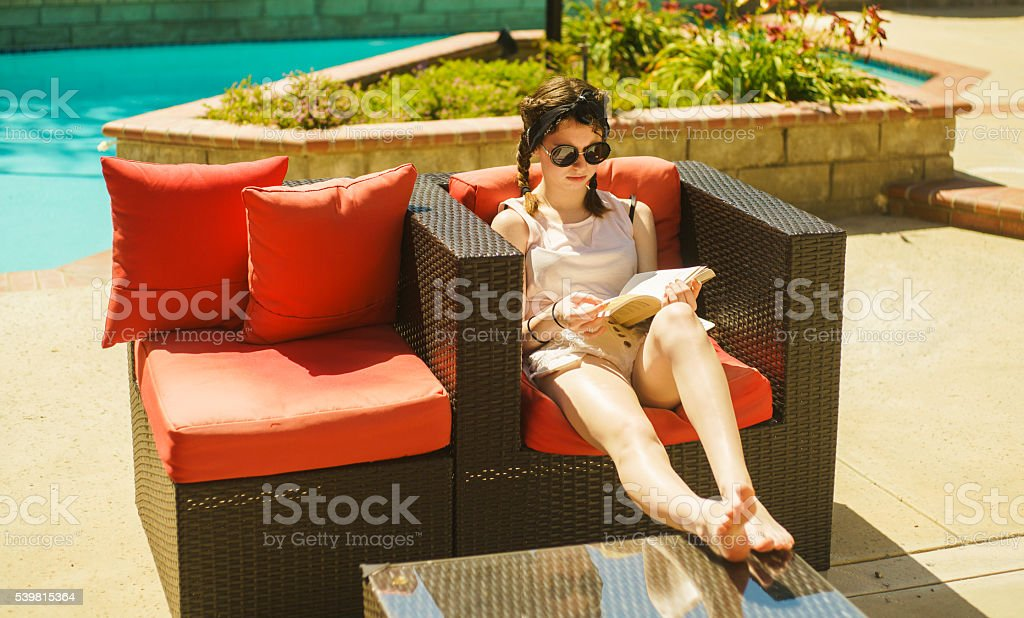 Teenager girl reading the book in the backyard's garden, California stock photo