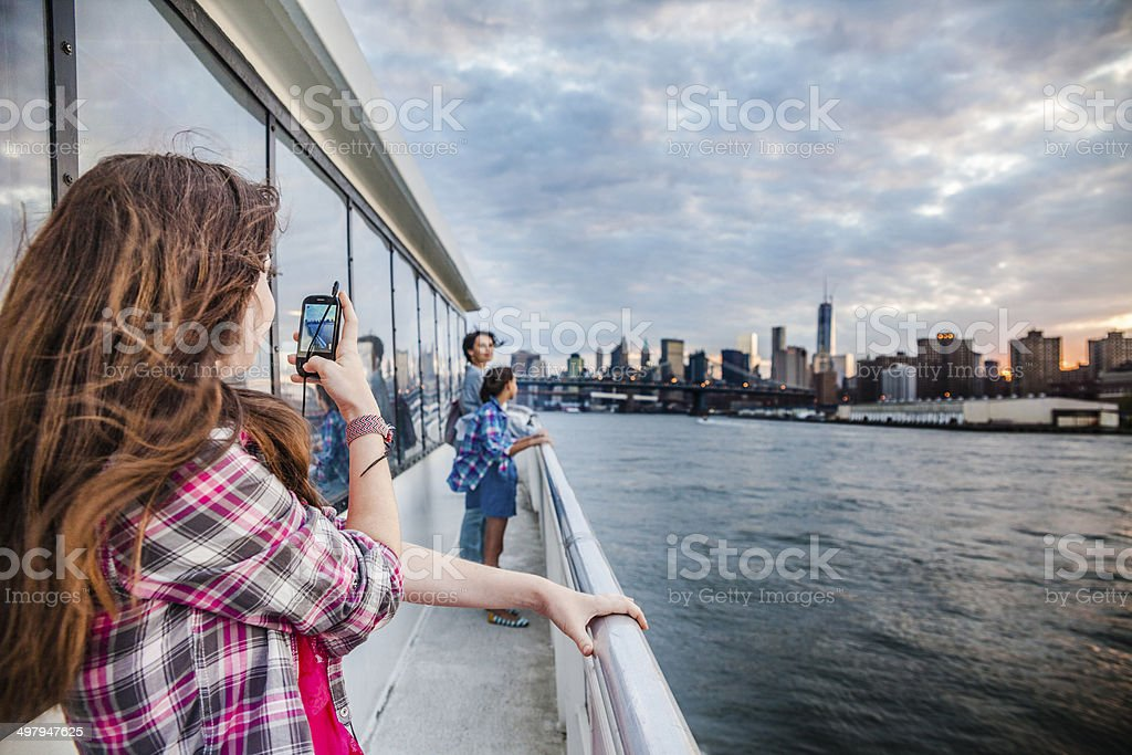 Teenager girl recording video with smart phone at ferry stock photo
